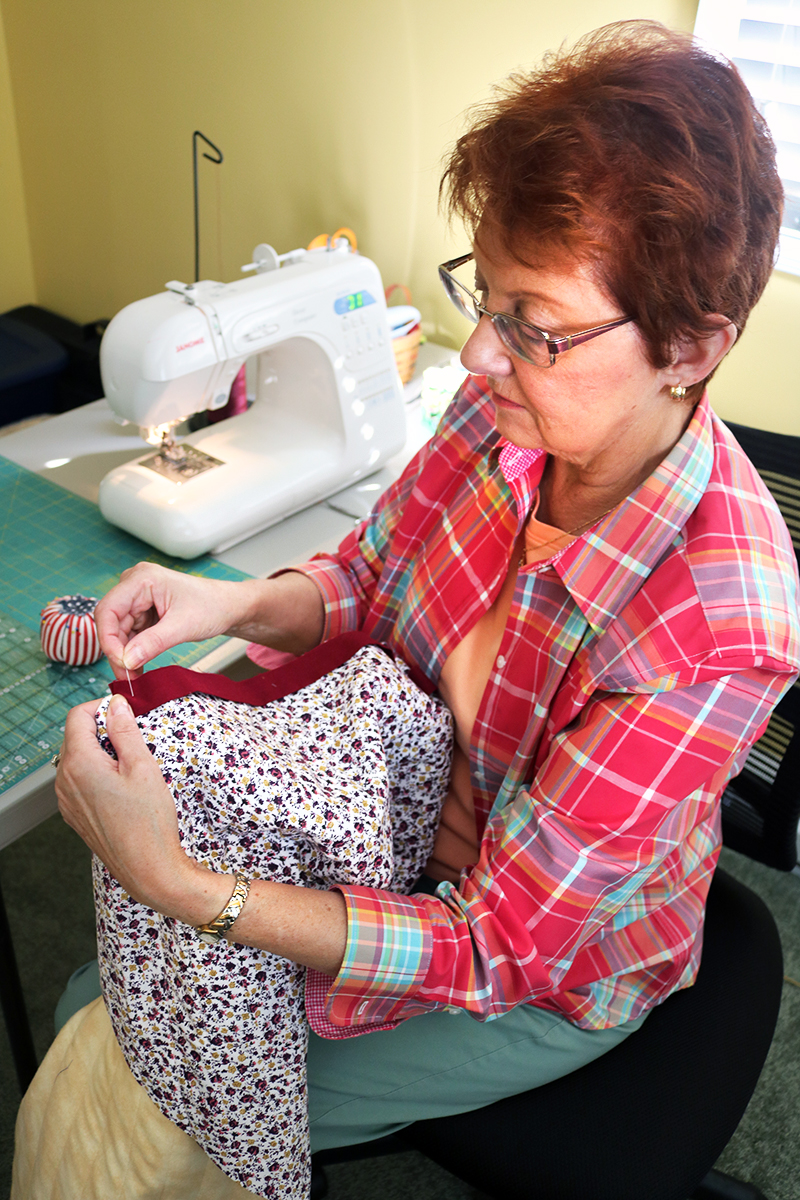 Senior volunteer sewing